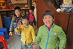 young boys saying hello in the front of a restaurant in Guilin, China