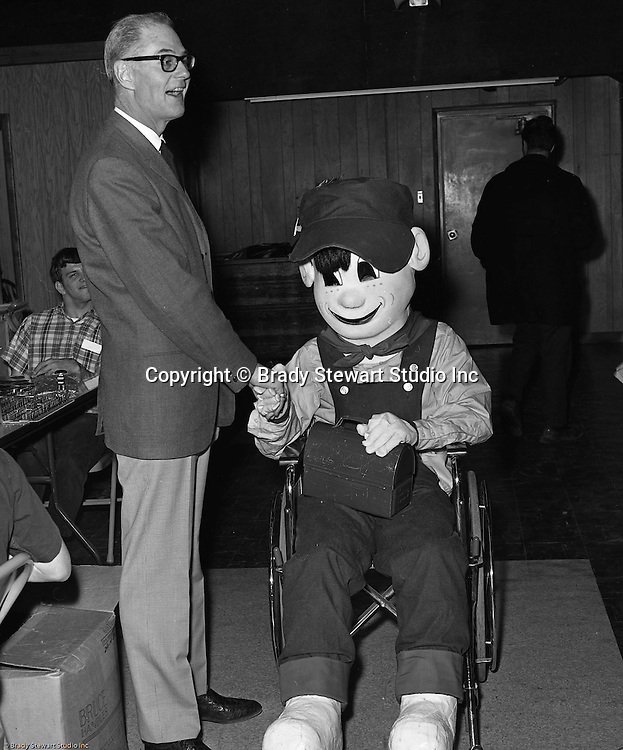 Pittsburgh PA:  Bob Prince at the Goodwill Industries facility in the Strip District.  Bob is talking with Good Willie, a young man who was in an advertising campaign to educate other wheel chair bound people that work opportunities exist at Goodwill Industries - 1966.