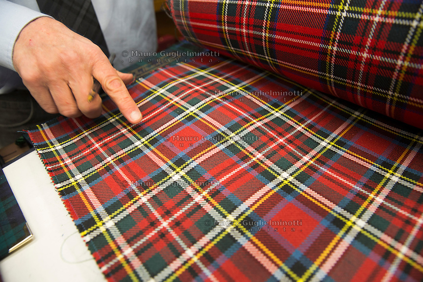 Il proprietario del negozio sfoglia i campionari di tessuti tartan e ne indica uno. The owner of the shop with th different tartan tissues