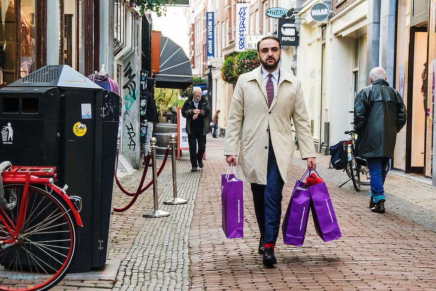 Nederland, Utrecht, 10 okt 2014<br /> Mensen op straat. Man in regenjas met tasjes van dure kledingzaken in zijn hand<br /> Foto: (c) Michiel Wijnbergh