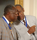 Hank Aaron and Bill Cosby share a thought after they received the Presidential Medal of Freedom from United States President George W. Bush during a ceremony in the East Room of the White House in Washington, D.C. on July 9, 2002..Credit: Ron Sachs / CNP