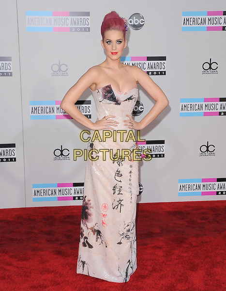 Katy Perry (wearing Vivienne Westwood).2011 American Music Awards - Arrivals held at Nokia Theatre LA Live, Los Angeles, California, USA..November 20th, 2011.ama amas ama's full length white Chinese sequins sequined draped dress strapless writing print blue peep toe snakeskin shoes cleavage hands on hips.CAP/RKE/DVS.©DVS/RockinExposures/Capital Pictures.