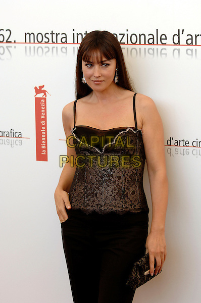 "MONICA BELLUCCI.photocall for ""The Bothers Grimm"".62nd International Film Festival,.Venice, 4th September 2005.half length La Biennale black corset strappy lace top skirt diamond dimante earrings clutch bag purse hand hip.Ref: PL.www.capitalpictures.com.sales@capitalpictures.com.©Capital Pictures."