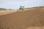 Red tractor ploughing field, Suffolk, England