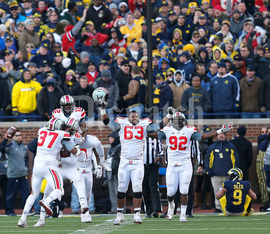 The Ohio State defense celebrates after intercepting the two point conversion during the fourth quarter of the NCAA football game at Michigan Stadium in Ann Arbor, Michigan on Saturday, November 30, 2013. (Columbus Dispatch photo by Jonathan Quilter)