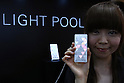 July 15, 2010 - Tokyo, Japan - A booth assistant introduces the Light Pool mobile handset from KDDI Corporation during the Expo Comm Wireless Japan 2010 - Mobile Power 2010 at Tokyo Big Sight, Japan, on July 15, 2010. The event held from July 14 to July 16, attracts around 37 000 professional buyers and 180 exhibiting companies from 10 countries looking to explore the latest wireless solutions, develop new business partners, or expand share of Japan's wireless market.