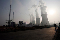 A man walks down a street next to a coal burning power plant in Yangquan, Shanxi Province, China. A survey from China's State Environmental Protection Agency shows that the province of Shanxi has the top three cities with the worst air pollution in China, with the city of Yangquan coming in second as it has a very high concentration of power plants using readily available coal to supply major cities centers such as Beijing with electricity..13 Oct 2006