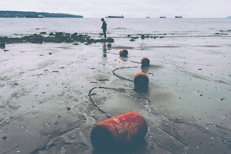 Woman standing near rocks at low tide with red chained floats snaking along wet sand.