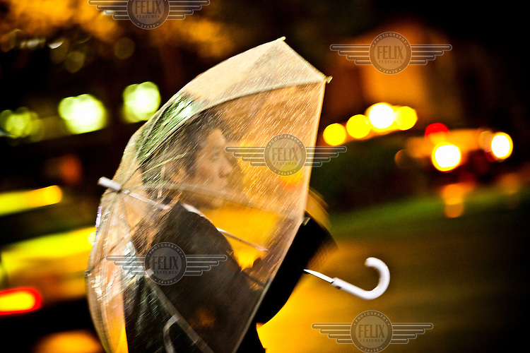 A businessman holds an umbrella in the rain in Tokyo.