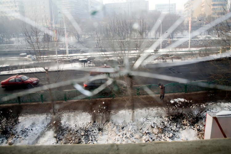 Broken glass obscures the view out a window of a hotel in Urumqi, Xinjiang, China.