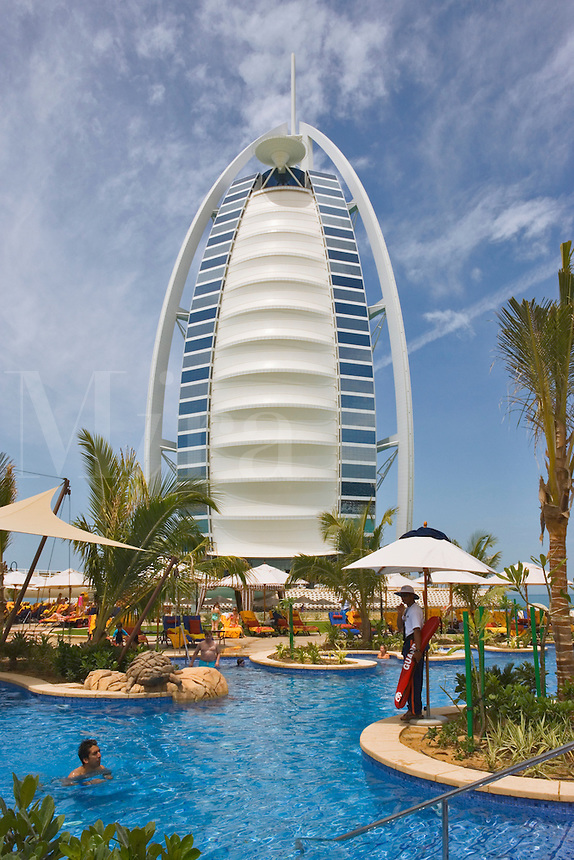 Burj al Arab Hotel, an icon of Dubai built in the shape of the sail of a dhow, stands on an artificial island just off Jumeirah Beach. View across pool at Jumeirah Beach Hotel.  Dubai. United Arab Emirates. Architects W.S. Atkins.