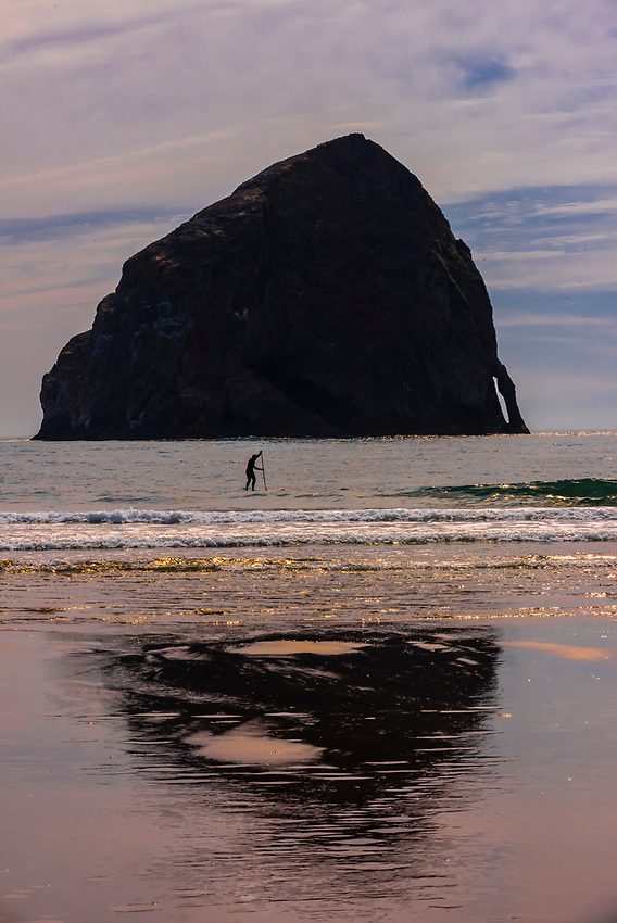 A man stand up paddleboarding with Haystack Rock behind, Cape Kiwanda, near Pacific City, Oregon USA.