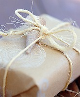 A gift wrapped in brown paper with a shell motif is personalised with a shell