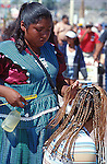 HAIRDRESSER BRAIDS WOMAN'S HAIR DURING STREET FESTIVAL
