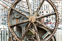 Up close photography of wheel on a rustin ship wais at a harbor in Scandinavia, with modern architecture build at the waterfront, as background.