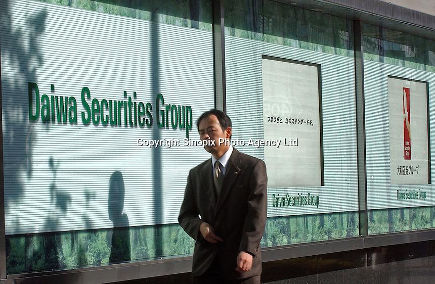 Businessmen pass through the sign of Daiwa securities Group, Tokyo, Japan..