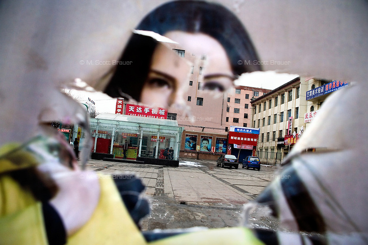 Torn advertisements surround a parking lot in Pingliang, Gansu, China.