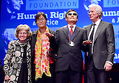 Chen Guangcheng, the blind Chinese legal activist, right center, poses for a group photo with Annette Lantos, wife of the late United States Representative Tom Lantos (Democrat of California), left, his wife, Yuan Weijing, left center, and actor Richard Gere, right, after accepting the Tom Lantos Human Rights Prize in the United States Capitol on January 29, 2013..Credit: Ron Sachs