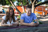 Young couple texting on mobile smart phones at East Austin Food Trailer Park on East 6th Street.