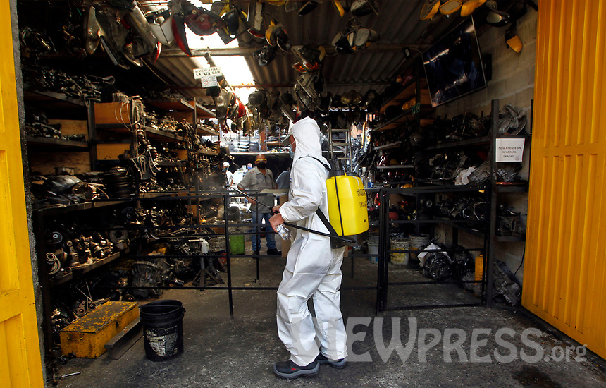 MEDELLIN, COLOMBIA-MAY 29: A police officer wearing protective clothing disinfects a mechanical workshop, in the neighborhood of Santa Cruz in Medellín, Colombia, on May 29, 2020.The mayor of Medellín and the private company offer a mask facial, antibacterial gel and alcohol for city communes As a preventive measure against the new coronavirus COVID-19. (Photo by Fredy Builes / VIEWpress via Getty Images)