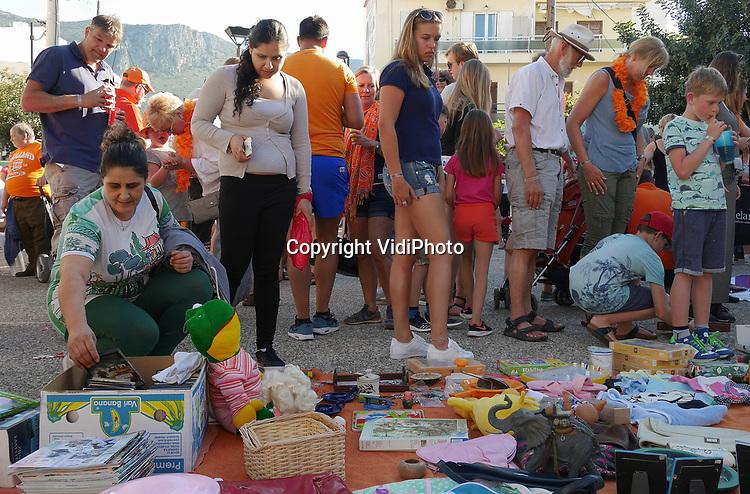 Foto: VidiPhoto<br /> <br /> CHERSONISSOS &ndash; De warmste Koningsdag sinds jaren, althans in Chersonissos op Kreta. Duizenden Nederlandse toeristen bezochten er donderdag luchtig gekleed de Koningsmarkt- en spelen in het centrum van de Nederlands-Griekse stad. De Oud-Hollandse spelen en BBQ werden georganiseerd door de Vereniging Nederlanders Chersonissos, een vereniging van Nederlanders die ter plaatse wonen en werken. De Koningsdag werd niet alleen georganiseerd uit nostalgie, maar ook om geld in te zamelen voor het Nederlandse schooltje ter plaatse. Sinds de Nederlandse overheid drie jaar geleden de subsidiekraan dichtdraaide kan de school met 30 leerlingen en twee leerkrachten nauwelijks nog het hoofd boven water houden. Zo&rsquo;n twintig Nederlandse bedrijven in Chersonissos helpen een financieel handje, maar verder moet de school zichzelf bedruipen. De vier andere Nederlandse scholen op Kreta hebben eveneens grote financi&euml;le problemen door de subsidiestop.