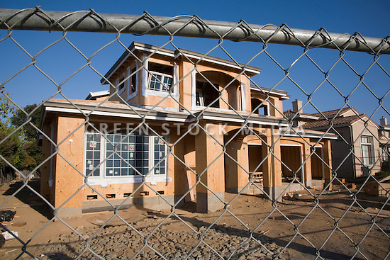 A large two-story wood frame home under construction behind a chain link fence. A finished home in the background foreshadows completion.