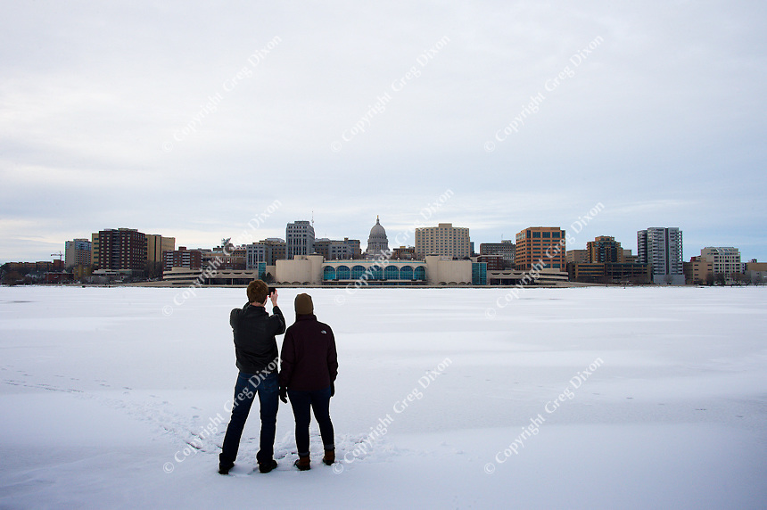 People stand on frozen Lake Monona, photographing Madison's State Capitol Building and Monona Terrace Community and Convention Center on Saturday