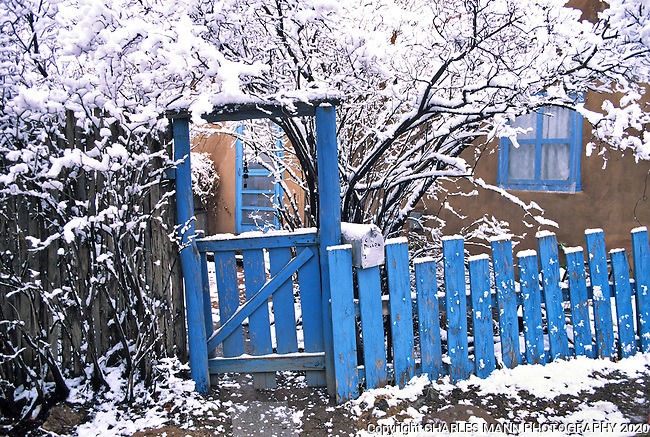 A leaning blue gate and fence in front of a Santa Fe adobe house become a colorful composition during a winter snowfall.