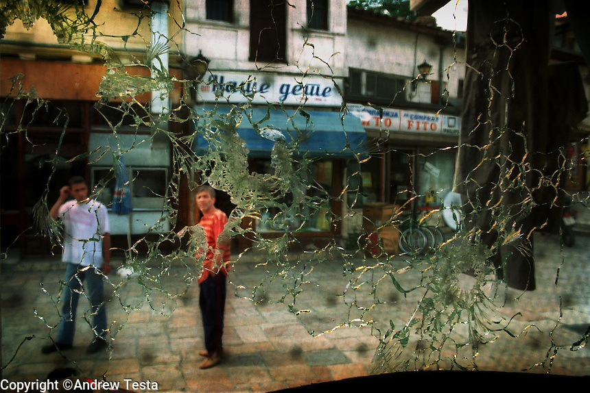 MACEDONIA. Skopje. 26 June 2001..Albanian passers by look through a bullet shattered shop front in the Albanian quarter of Skopje. The shots were fired during anti Government riots by Macedonian Slavs dissatisfied with the ceasefire agreement with the Albanian rebels of the National Liberation Army..©Andrew Testa