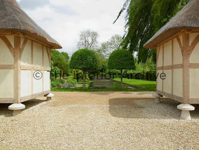 Matching thatched pavilions face the formal garden