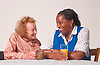 Carer sitting at table with elderly woman talking and smiling,