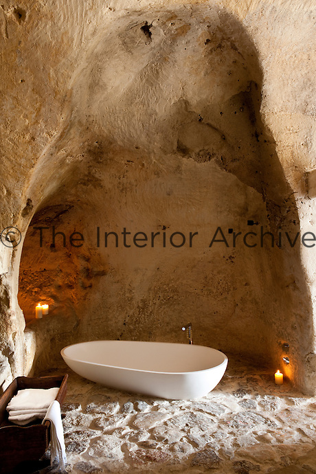 The free standing bath has been cleverly placed under a natural alcove in the bathroom at the unique Albergo Diffuso Le Grotte della Civita in Southern Italy, housed in  restored caves