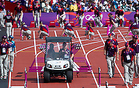 03 AUG 2012 - LONDON, GBR - Gamesmakers clear hurdles after the women's heptathlon 100m hurdles heats during the London 2012 Olympic Games athletics at the Olympic Stadium in the Olympic Park in Stratford, London, Great Britain (PHOTO (C) 2012 NIGEL FARROW)