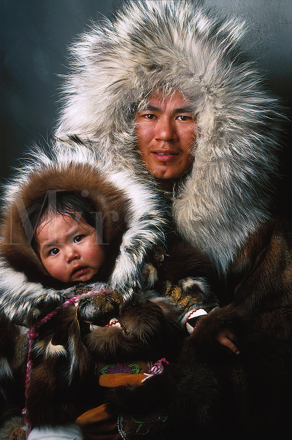 Portrait of a Native Alaskan Inupiat father and infant daughter in traditional fur coats and hoods. Alaska.