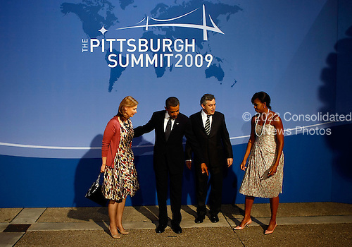 Pittsburgh, PA - September 24, 2009 -- United States President Barack Obama (2L) and U.S. first lady Michelle Obama (R) welcome British Prime Minister Gordon Brown (2R) and his wife Sarah Brown to the welcoming dinner for G-20 leaders at the Phipps Conservatory on Thursday, September 24, 2009 in Pittsburgh, Pennsylvania. Heads of state from the world's leading economic powers arrived today for the two-day G-20 summit held at the David L. Lawrence Convention Center aimed at promoting economic growth..Credit: Win McNamee / Pool via CNP