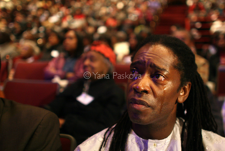 "Malik Camara, 47, teacher, from Chicago, tears up as he watches the inauguration of Barack Obama as President of the United States in the theater of the DuSable Museum of African-American History in Chicago, Illinois, on the Presidential Inauguration Day, Tuesday, January 20, 2009.  Camara said, ""I expect Obama to stay grounded, spiritually, mentally, and physically, because a lot in his job will be overwhelming, but as long as he stays grounded, he will be okay."" Camara's phone number: 773.239.1771 (Photo by Yana Paskova for The New York Times)..Assignment ID: 30075164A"