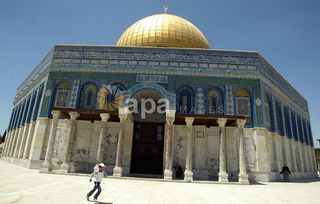 A Palestinian boy walks in front of the dome of the rock at Al-Aqsa mosque in the old city of Jerusalem on July 12, 2009. Photo by Mahfouz Abu Turk
