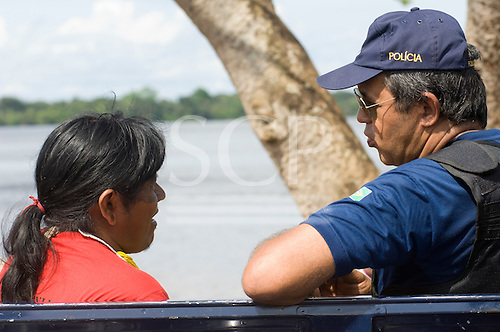 "Altamira, Brazil. ""Xingu Vivo Para Sempre"" protest meeting about the proposed Belo Monte hydroeletric dam and other dams on the Xingu river and its tributaries. A policeman chats to  a Kayapo Indian."