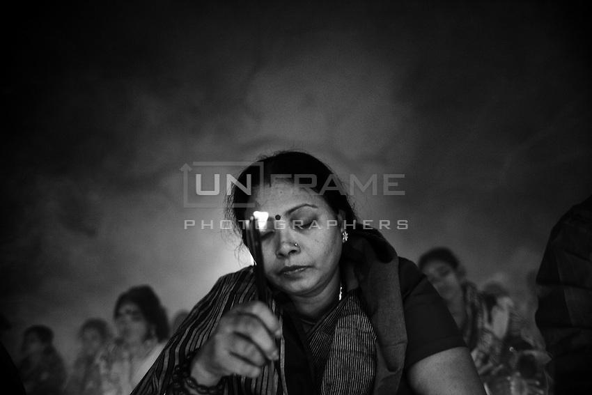 A Hindu woman prays holding an incense sticks during  the Kartik Brati or Rakher Upobash religious festival in Barodi,  Near Dhaka, Bangladesh