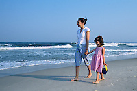Mother and daughter, walking along the beach, holding hands.  Long Beach Island, New Jersey