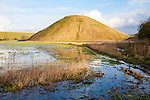 Silbury Hill ancient neolithic manmade chalk mound in Avebury, Wiltshire, England with flood water in the foreground