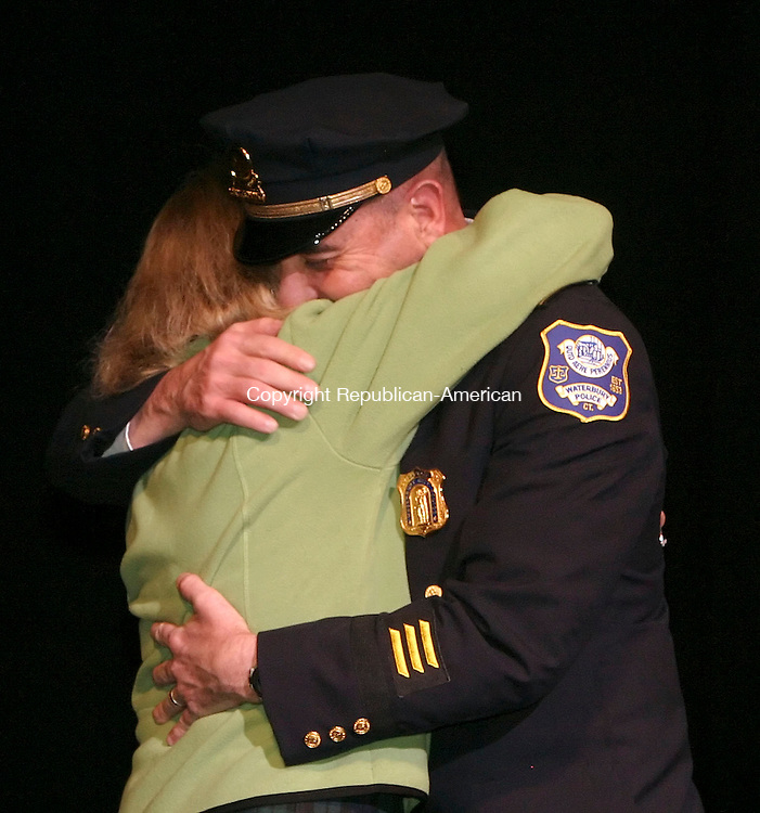 WATERBURY, CT 12/07/07- 120707BZ07- Tova McGrew gets a hug from her husband Capt. Sherman McGrew after pinning on his badge during a promotion ceremony as part of the Waterbury Police Department Police Academy graduation excercises at the Palace Theater Friday night.  McGrew was promoted without his knowledge by order of Waterbury Mayor Michael J. Jarjura.<br /> Jamison C. Bazinet Republican-American