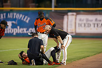 AZL Giants manager Hector Borg (13) looks over a trainer's evaluation of right fielder Diego Rincones (35) after a collision behind first base with second baseman Robert Antunez (34) during the game against the AZL Reds on August 12, 2017 at Scottsdale Stadium in Scottsdale, Arizona. AZL Giants defeated the AZL Reds 1-0. (Zachary Lucy/Four Seam Images)