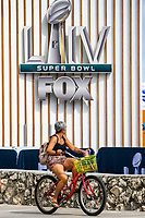MIAMI, USA - January 24: A woman rides her bike near the Super Bowl XLIV fan zone on January 24, 2020 in Miami Beach, USA.  The Super Bowl XLIV will take place in the Hard Rock Stadium in Miami between the teams 49ers vs. Chiefs, and it will be played on Sunday, Feb. 2, 2020. (Photo by VIEWpress)