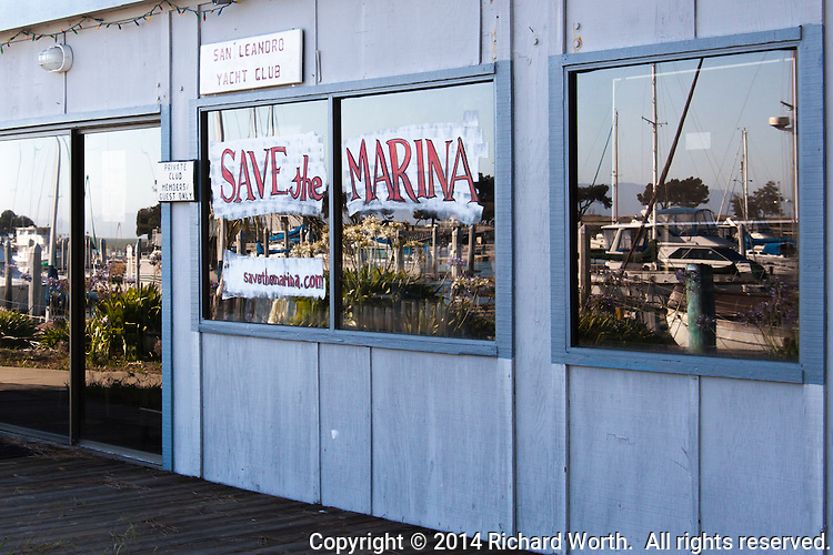 "Windows of the San Leandro Yacht Club reflect the marina and its dwindling residents while calling out ""Save the Marina""."