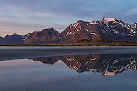 Midnight sun mountain reflection on Ytresand beach, Moskenesøy, Lofoten Islands, Norway