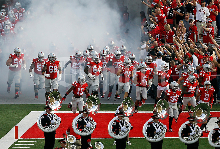 Ohio State football players exit the tunnel of smoke and take the field prior to the NCAA football game against the Cincinnati Bearcats at Ohio Stadium in Columbus on Sept. 27, 2014. (Adam Cairns / The Columbus Dispatch)