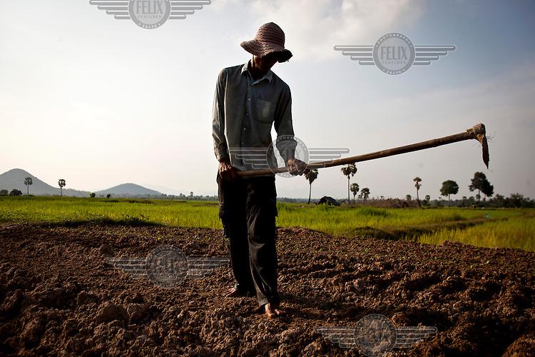 Ker Heun hoes land owed by his mother, Svey Monin, in Prey Cheuteal village.