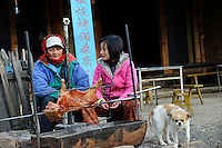 CHINA Yunnan Lugu Lake, women grill pig /CHINA Provinz Yunnan , Lugu See, Frauen grillen ein Spanferkel