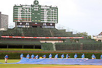The Chicago Cubs grounds crew pulls the tarp after a rain delay during the Under Armour All-American Game at Wrigley Field on August 13, 2011 in Chicago, Illinois.  (Mike Janes/Four Seam Images)